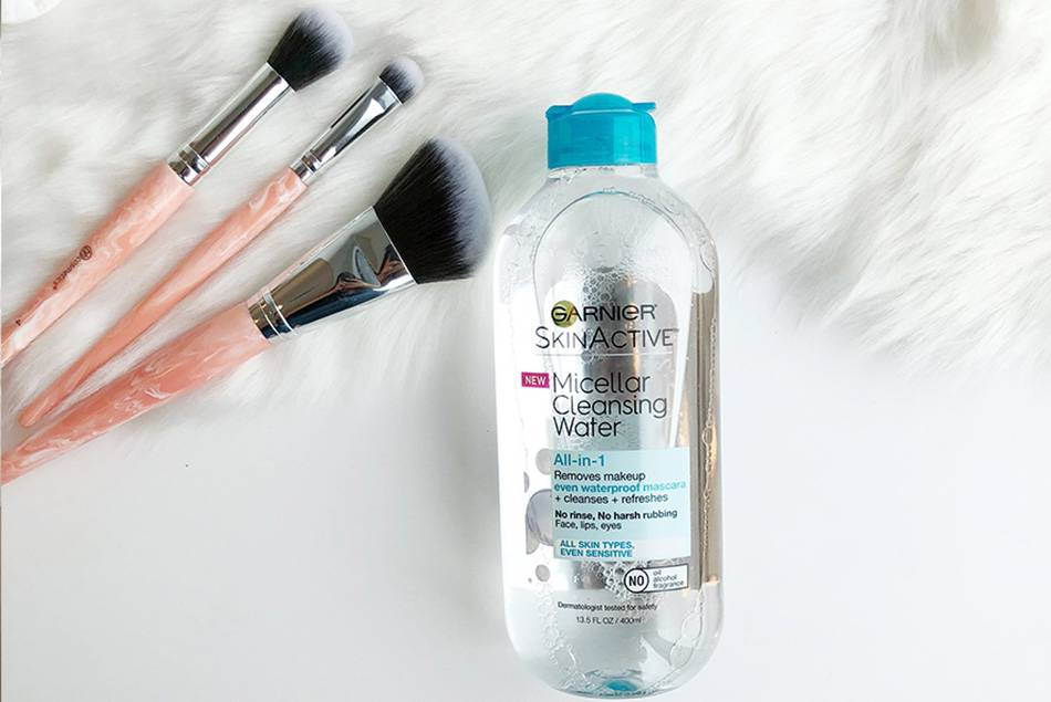 Garnier Skin Active Micellar Cleansing Water All-in-1 with Blue Cap beside a white fur rug with three makeup brushes on it.