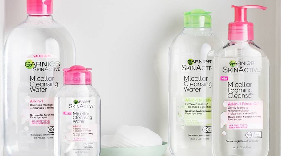 A white shelf with Garnier Skin Active Micellar Cleansing Water All-in-1 with Pink Cap, Micellar Cleansing Water All-in-1 with Pink Cap Travel Size, Micellar Foaming Cleanser All-in-1 Rinse Off with Pink Cap, Micellar Cleansing Water All-in-1 Mattifying with Green Cap, and a seafoam green bowl of makeup pads on the top shelf and Micellar Cleansing Water All-in-1 with Blue Cap, Micellar Cleansing Water All-in-1 with Pink Cap, and Micellar Eye Makeup Remover Pads on on the bottom shelf with a white rose in a clear vase.