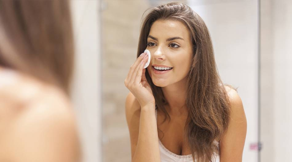 Woman removing makeup with a pad in her bathroom.