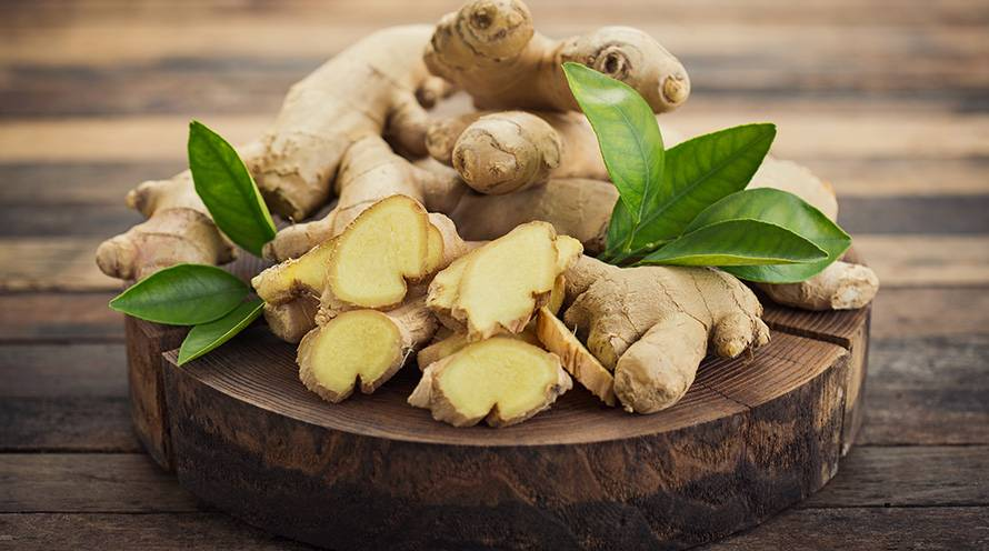 A pile of ginger lying on top of a wooden tray.