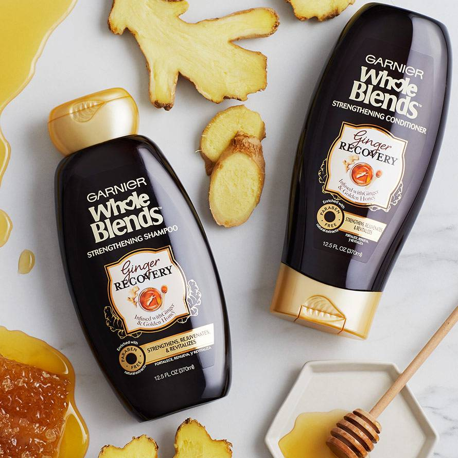 Whole Blends Ginger Recovery Strengthening Shampoo and Conditioner lying on top of a white marble countertop, surrounded by honey and sliced ginger.