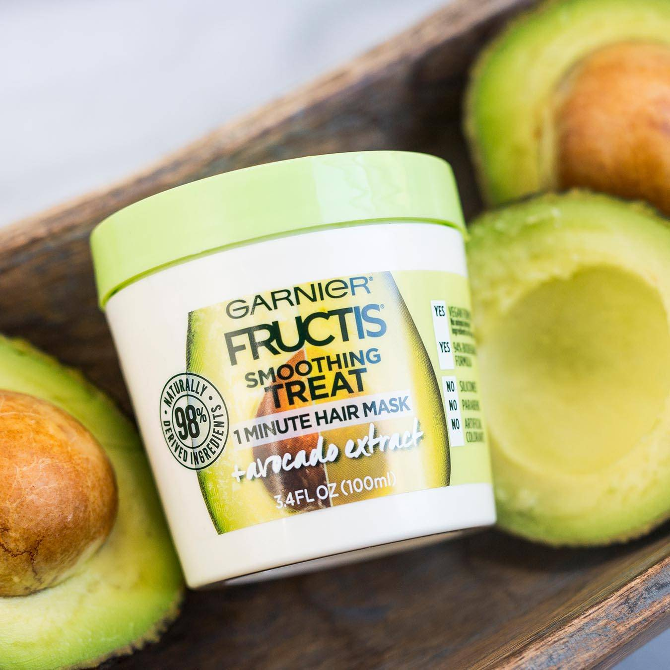 Garnier Fructis Smoothing Treat 1 Minute Hair Mask with Avocado Extract in a wooden trough next to halved avocados on a white marble background.