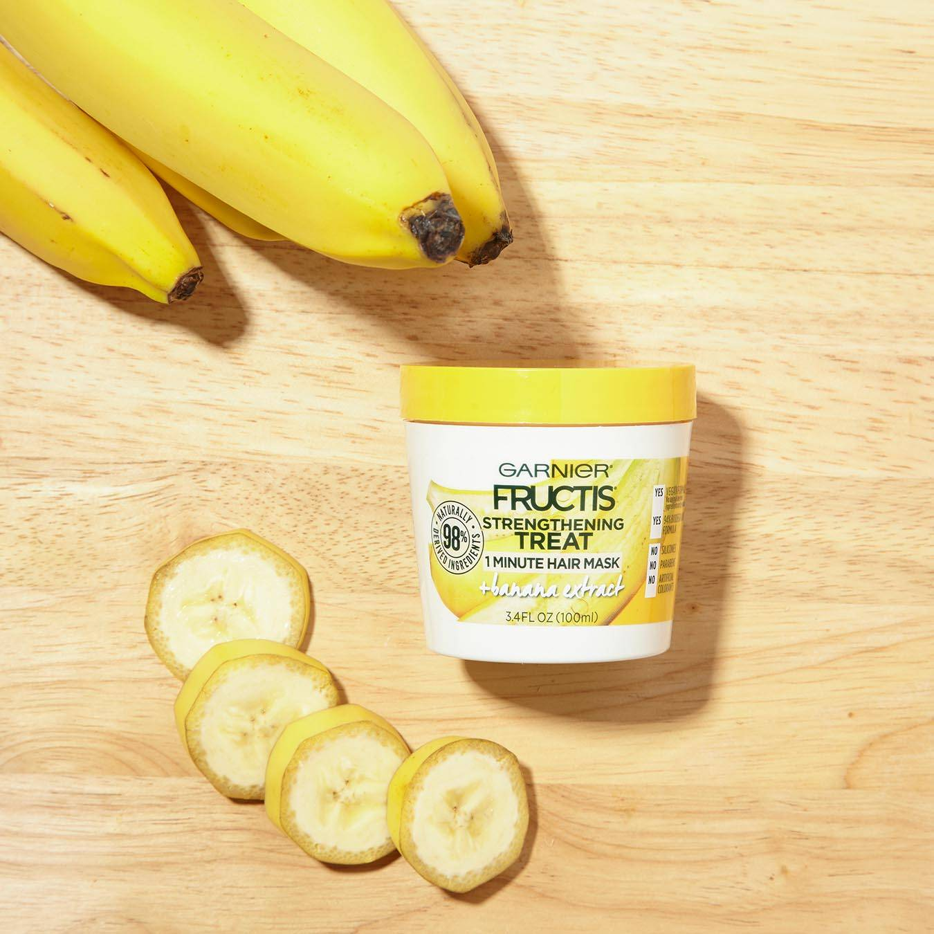 Garnier Fructis Strengthening Treat 1 Minute Hair Mask with Banana Extract on a wooden background next to a bunch of bananas and banana slices.