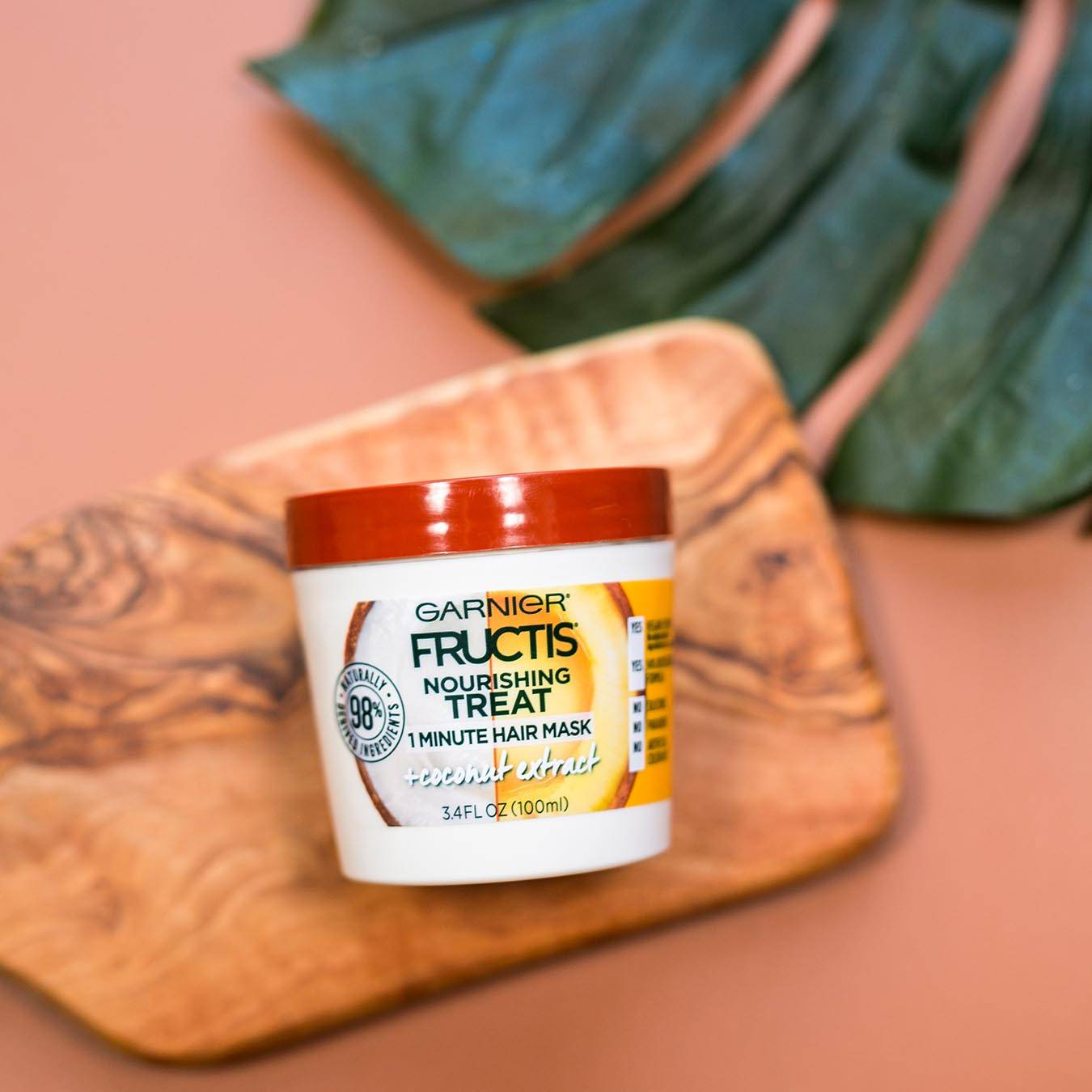 Garnier Fructis Nourishing Treat 1 Minute Hair Mask with Coconut Extract on a wooden cutting board beside a palm frond on a muted red background.