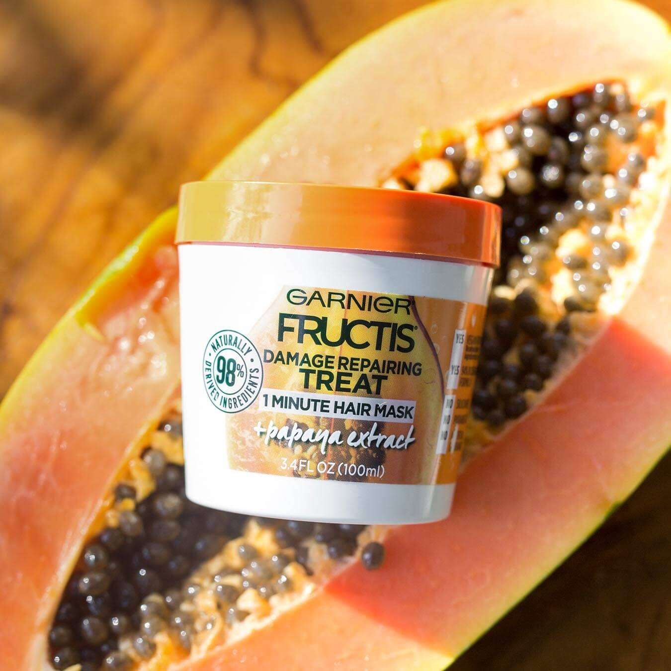 Garnier Fructis Damage Repairing Treat 1 Minute Hair Mask with Papaya Extract sitting on half a papaya on a wooden table.