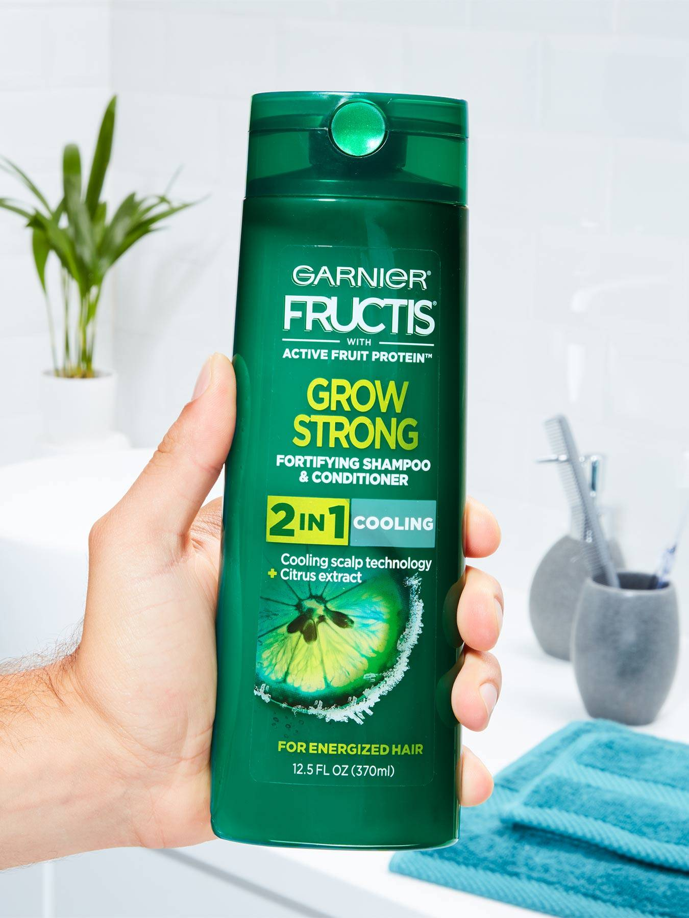 Hand holding Cooling 2-In-1 Shampoo and Conditioner for Men in a white bathroom with a blue towel, silver cups with toothbrushes, and a plant.