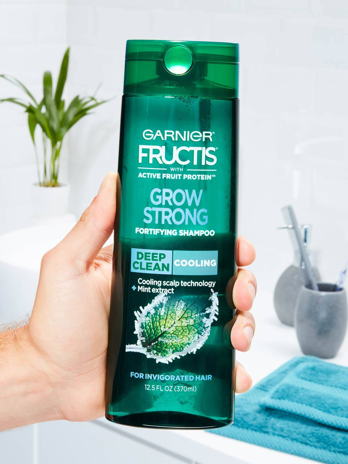 Hand holding Cooling Deep Clean Shampoo for Men for Invigorated Hair in a white bathroom with a blue towel, silver cups with toothbrushes, and a plant.
