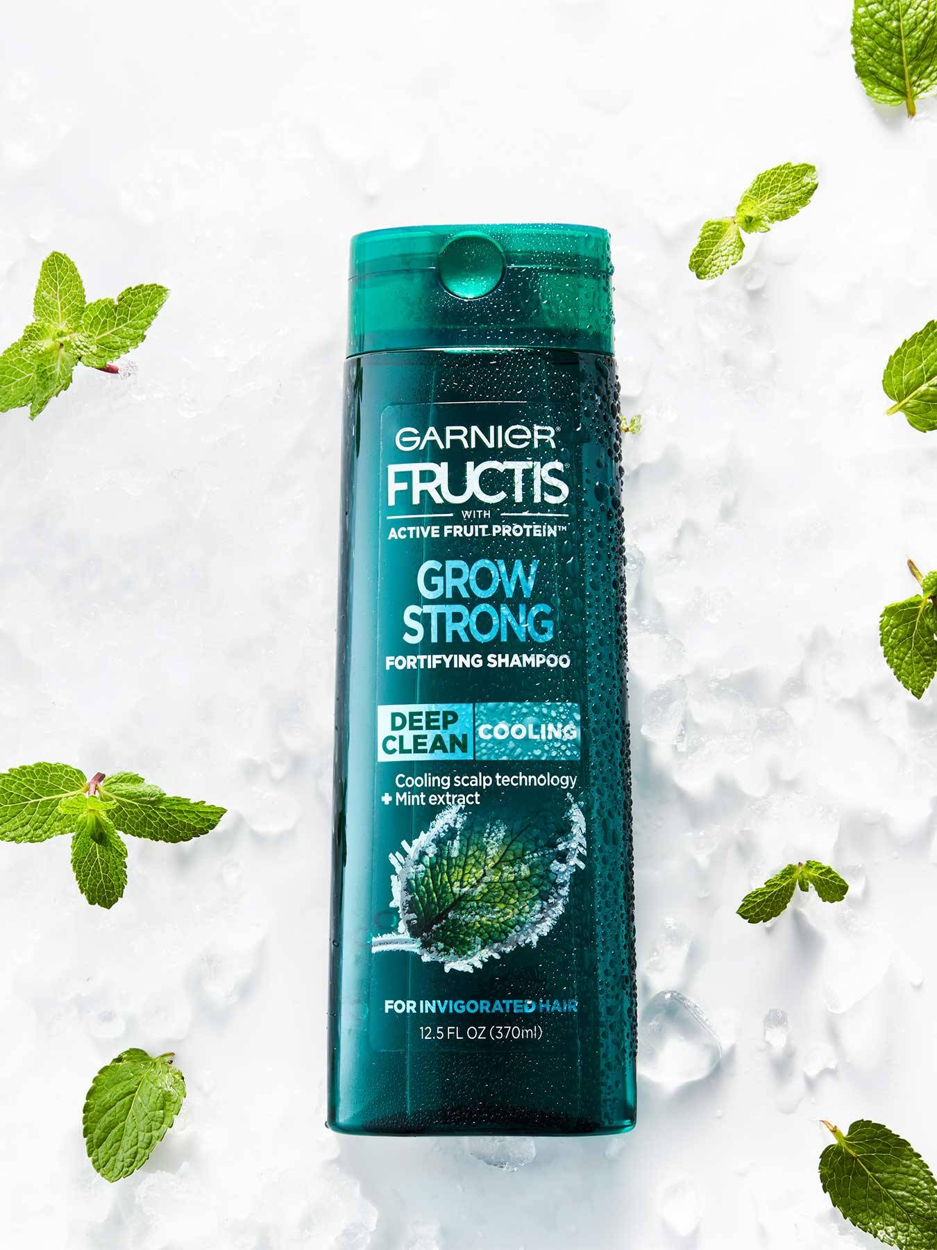 Cooling Deep Clean Shampoo for Men for Invigorated Hair on a bed of ice with mint leaves.