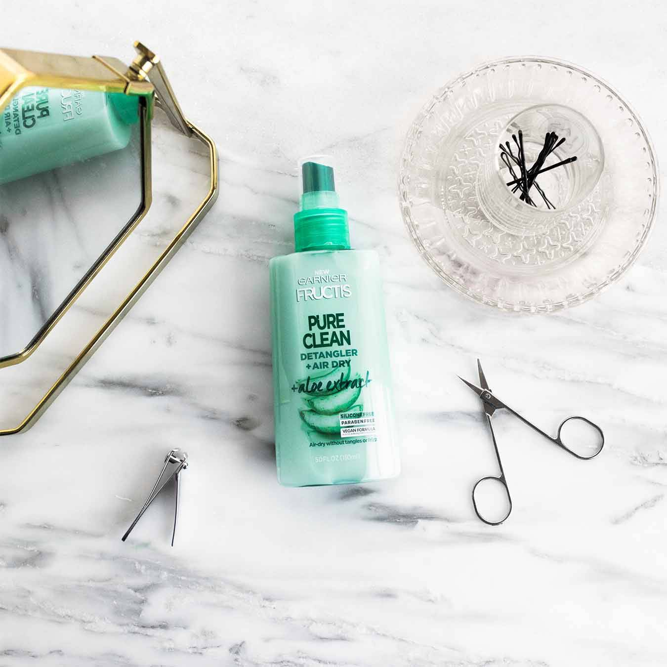 Garnier Fructis Pure Clean Detangler with Aloe Extract reflected in a gold mirror on white marble next to facial hair scissors, fingernail clippers, and a glass cup filled with bobby pins sitting on a glass plate.