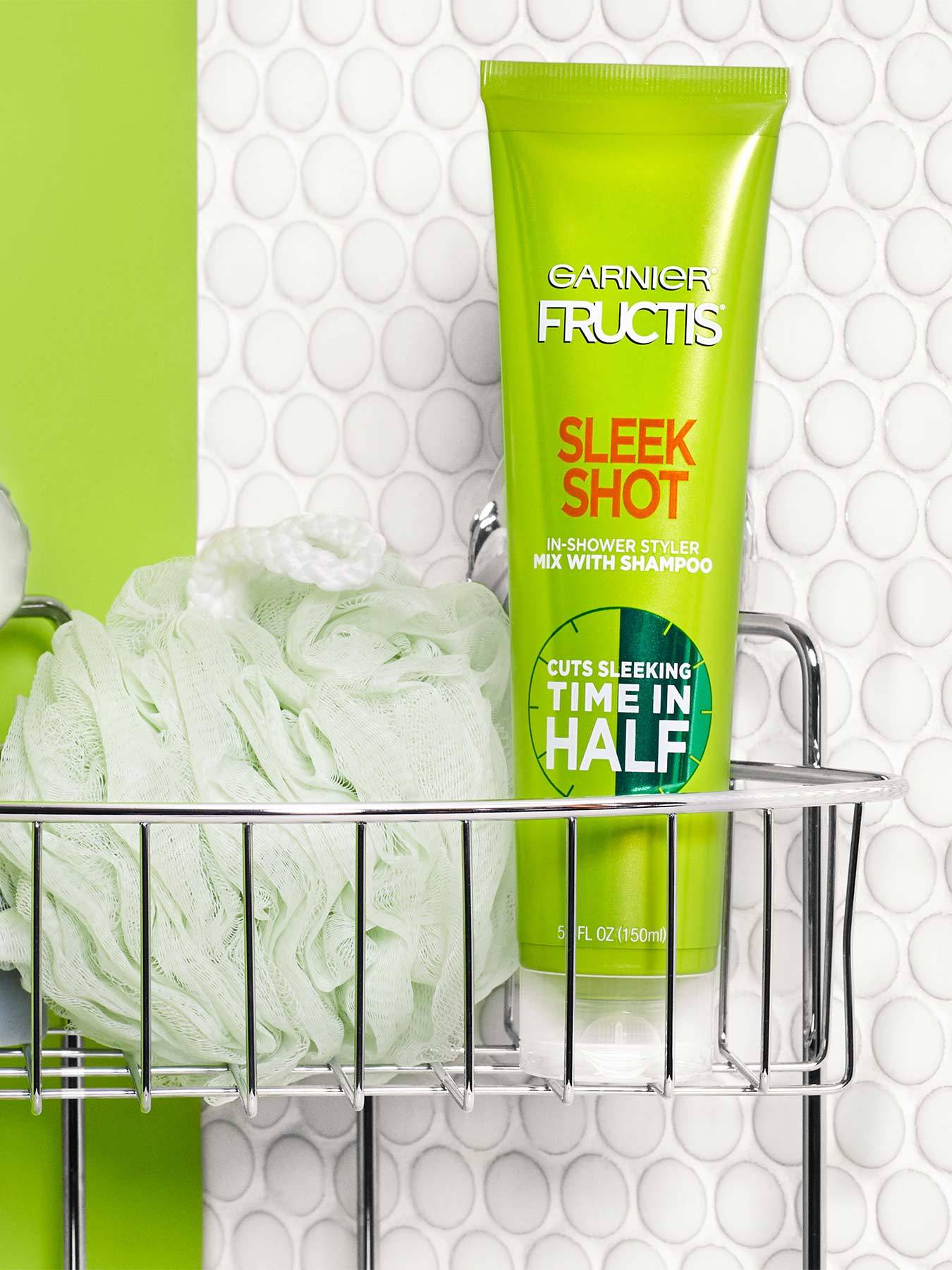 Sleek Shot In-Shower Styler in a shower rack with green-grey soap and a light green bath poof in a green and dotted-white bathroom.