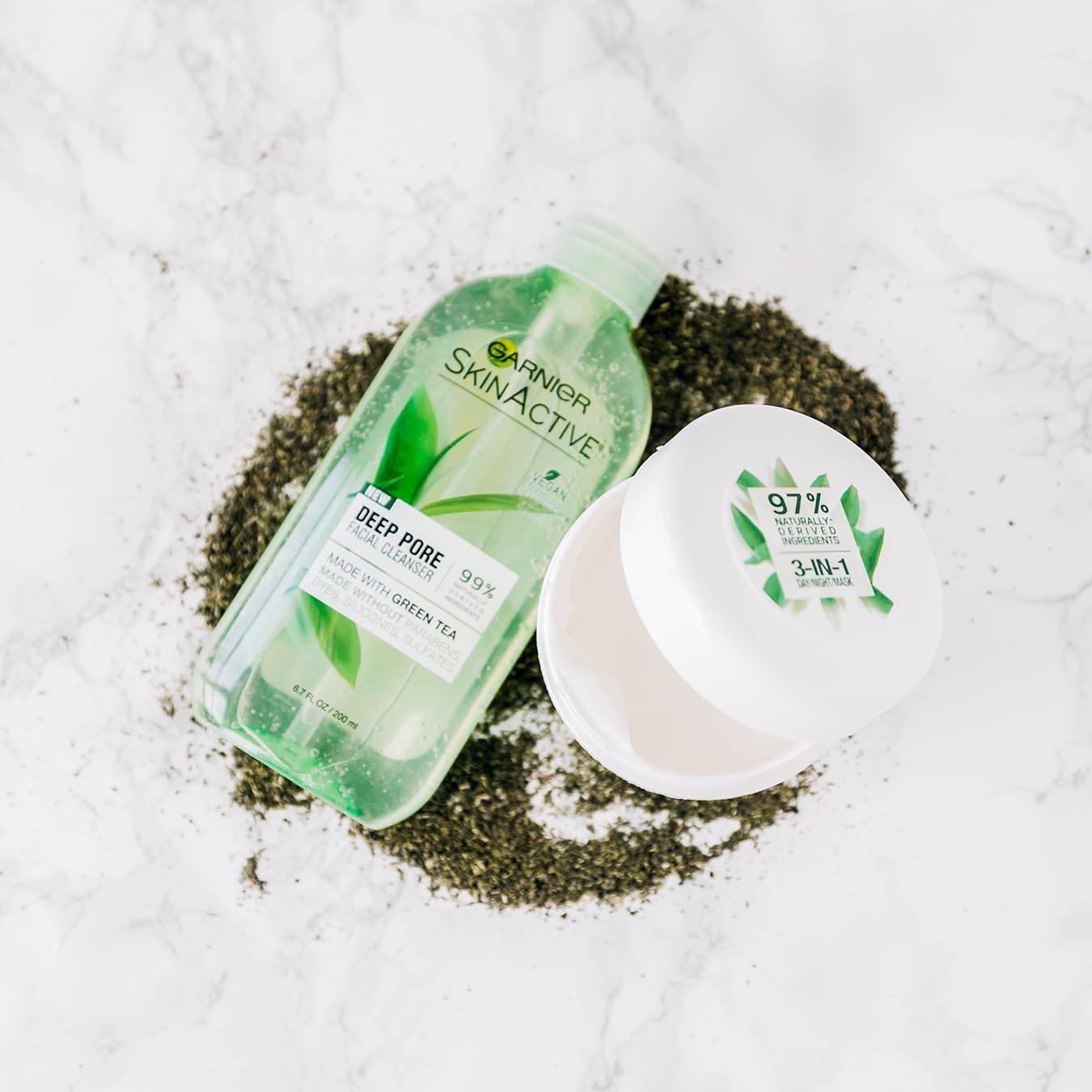 Garnier SkinActive 3-in-1 Day/Night Mask ajar with Green Tea and SkinActive Deep Pore Cleanser sitting in a pile of powdered tea leaves on white marble.