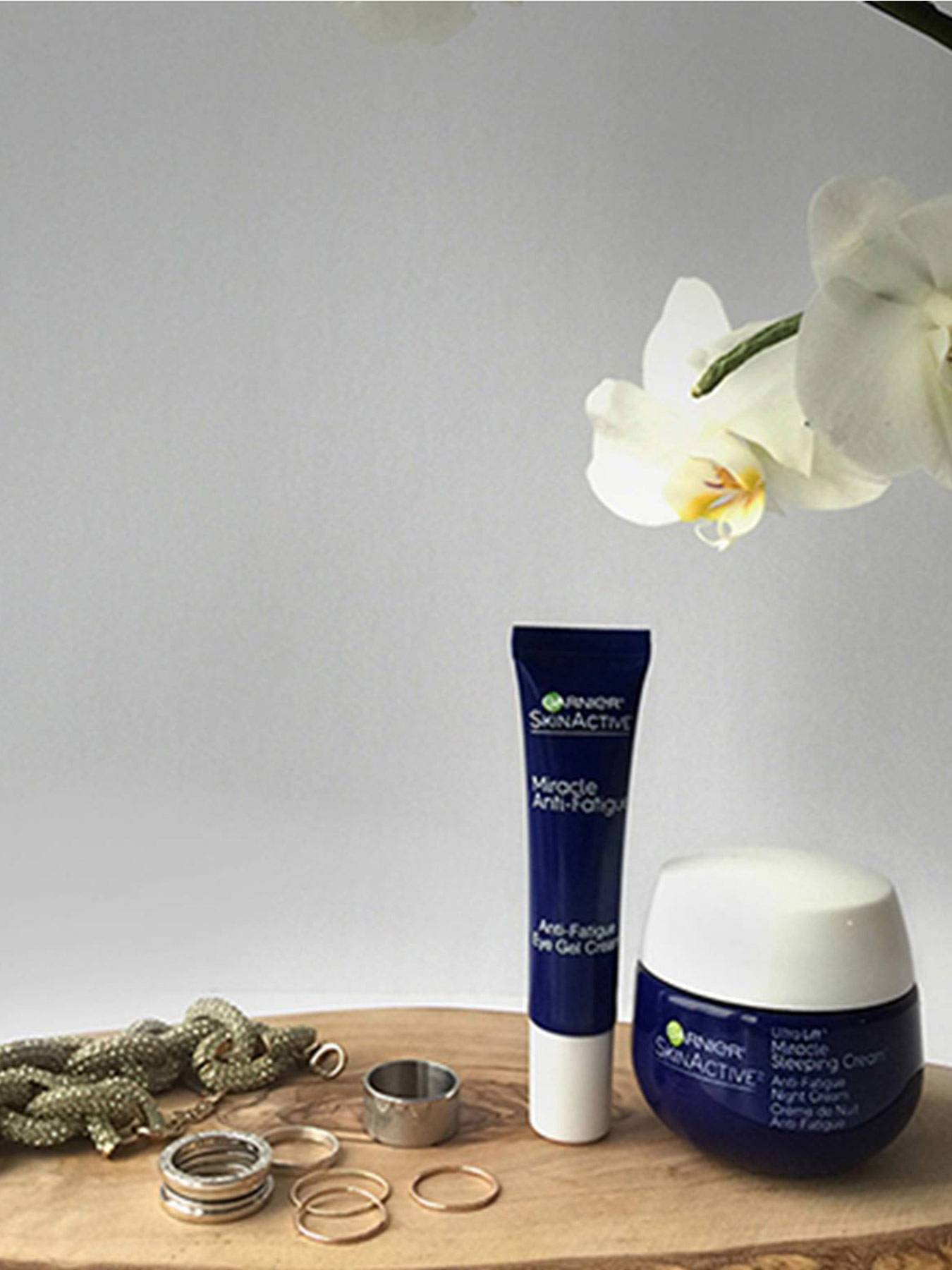 A tube of Miracle Anti-Fatigue Eye Gel Cream and a jar of Miracle Anti-Fatigue Night Cream sit on a wooden table beside various silver rings and a thick braided necklace on a wooden table beside a white orchid on a grey background.