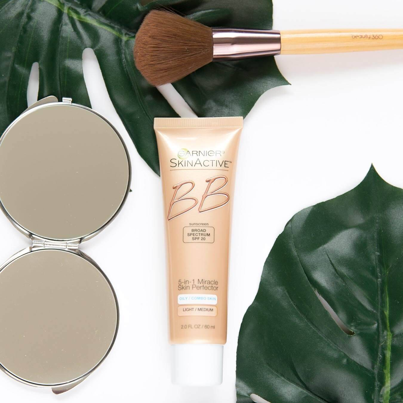 Garnier SkinActive BB Broad Spectrum SPF 20 5-in-1 Miracle Skin Perfector for Light/Medium on a white background next to two palm fronds, thick makeup brush, and a folding mirror.