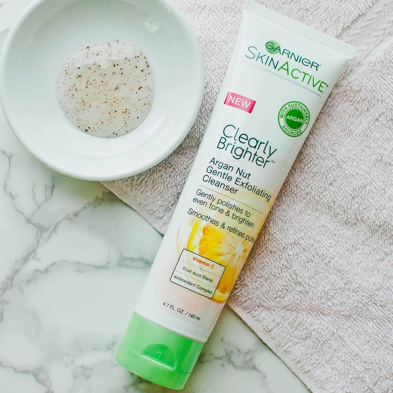 Garnier SkinActive Clearly Brighter Argan Nut Gentle Exfoliating Cleanser on a tan towel and white bowl holding a small amount of product on white marble.