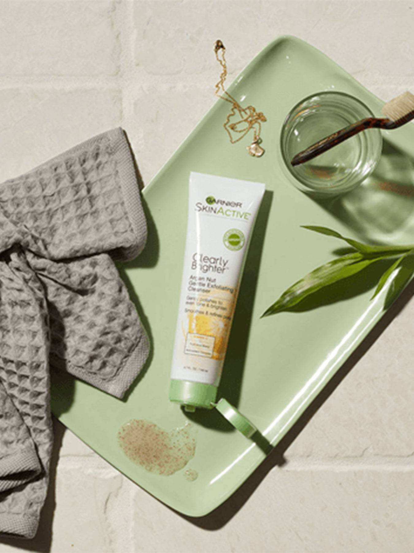 Clearly Brighter Argan Nut Gentle Exfoliating Cleanser open with some product spilled on a green tray holding a glass with a toothbrush, a gold necklace and pendant, a leaf, and a grey washcloth.