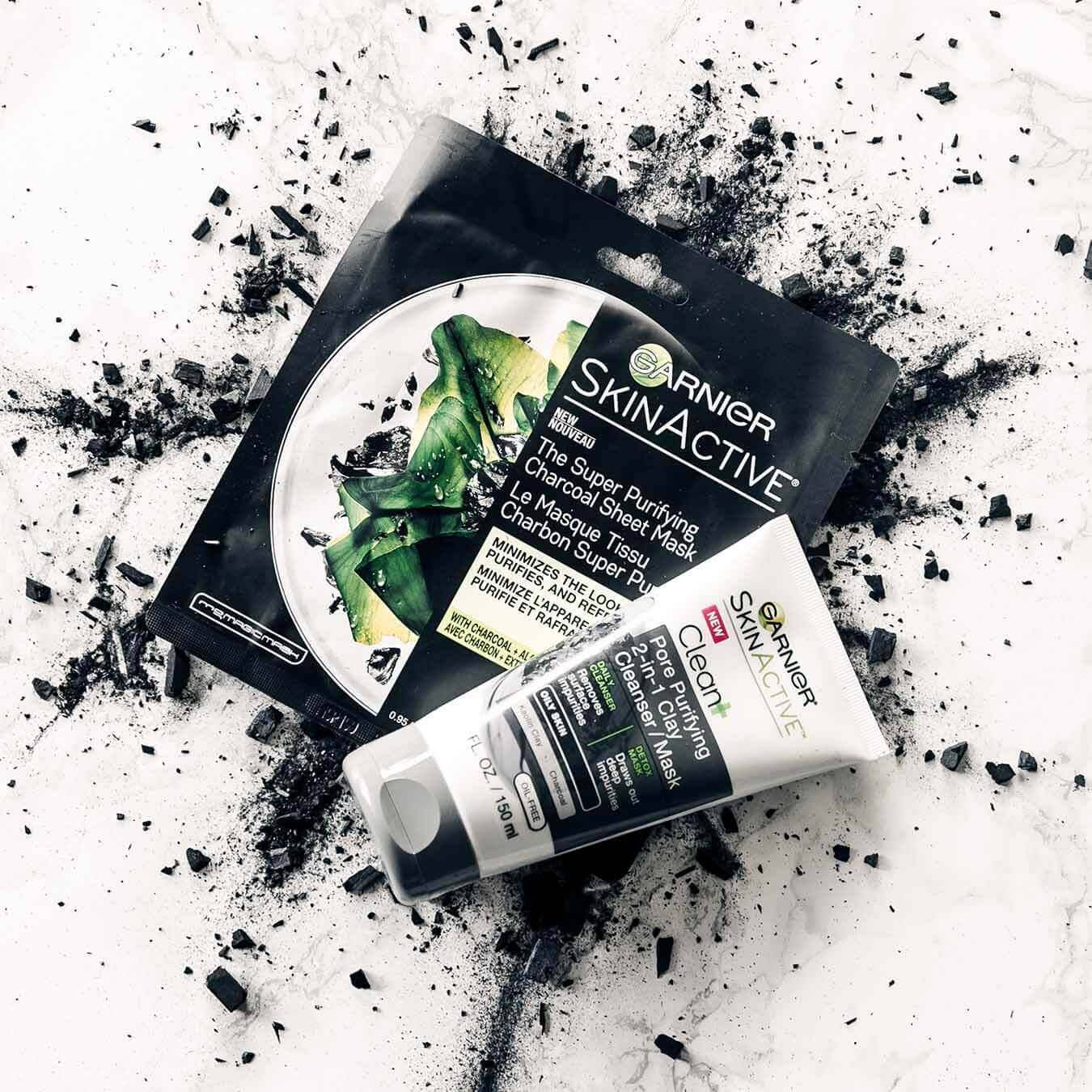 Garnier SkinActive Super Purifying Charcoal Sheet Mask and SkinActive Clean+ Blackhead Eliminating Scrub on an explosion of charcoal chunks and powder on pinkish white marble.