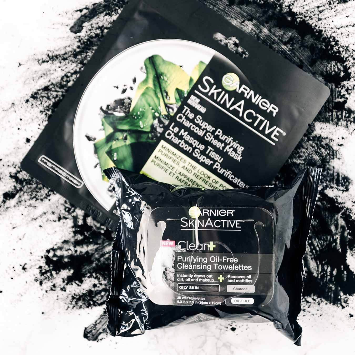 Garnier SkinActive Super Purifying Charcoal Sheet Mask and SkinActive Clean+ Purifying Oil-Free Cleansing Towelettes on an explosion of charcoal powder on pinkish white marble.