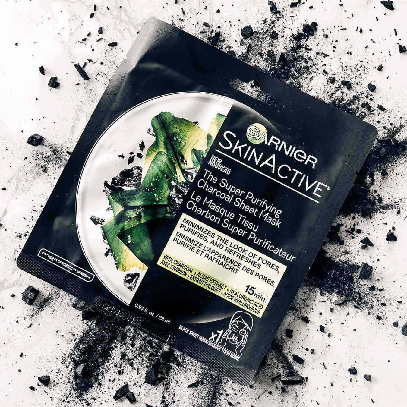 Garnier SkinActive Super Purifying Charcoal Sheet Mask on an explosion of charcoal chunks and powder on pinkish white marble.