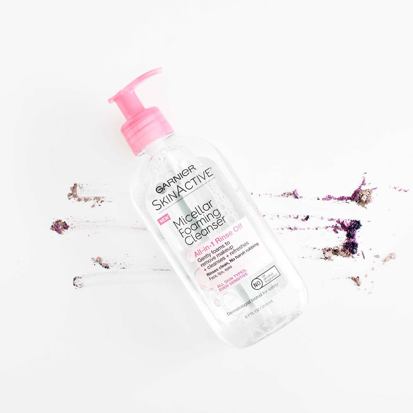 Garnier SkinActive Micellar Foaming Cleanser All-in-1 Rinse Off with pink pump on a white background smudged with tan and purple blush.