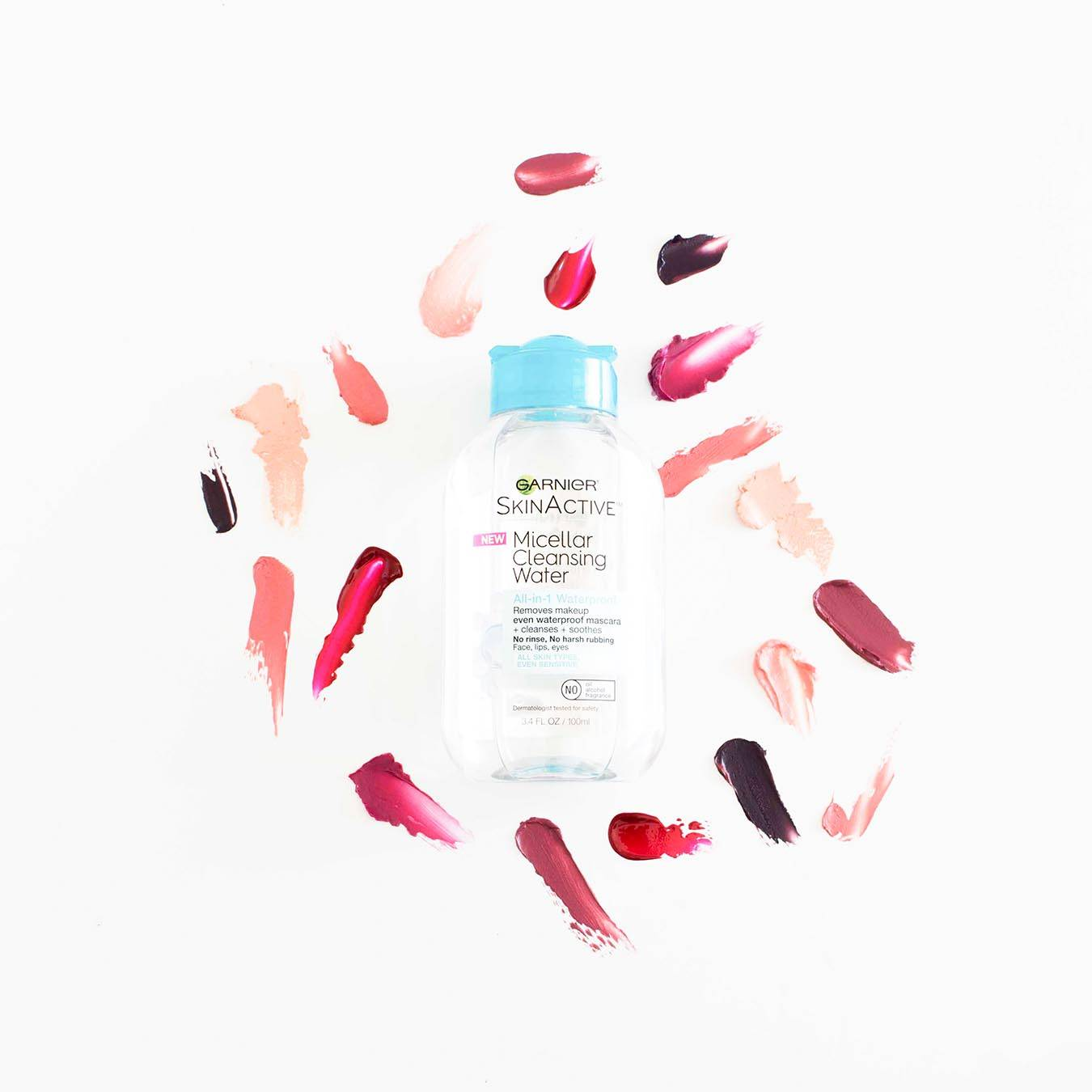 Garnier SkinActive Micellar Cleansing Water All-in-1 Waterproof 3.4 oz with blue lid on white background with various smudges of red and pink lipstick.