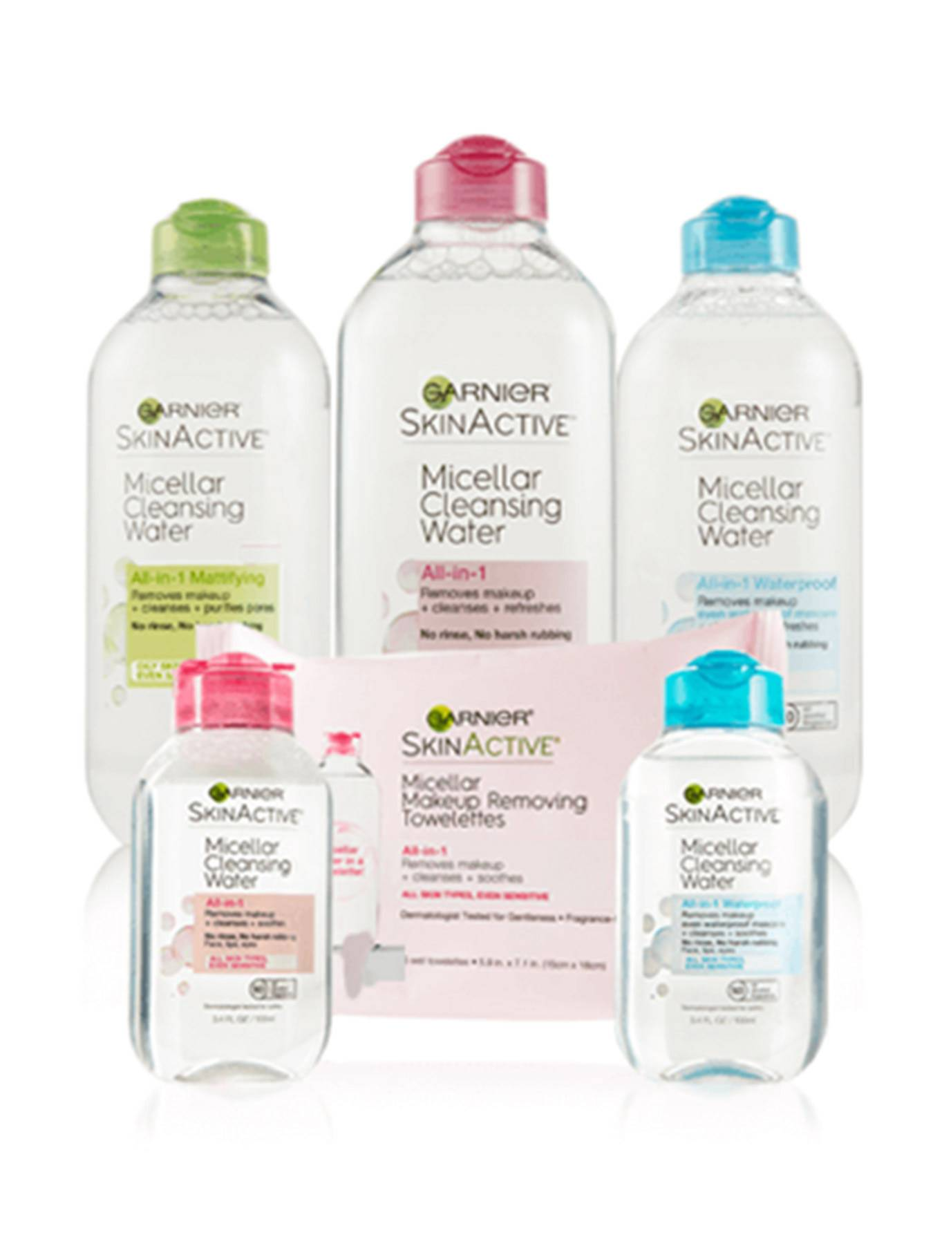 Micellar Cleansing Water All-in-1 Mattifying, All-in-1, and All-in-1 13.5oz bottles sit behind the Micellar Makeup Removing Towelettes and the All-in-1 and All-in-1 Waterproof Travel size bottles on a white reflective background.