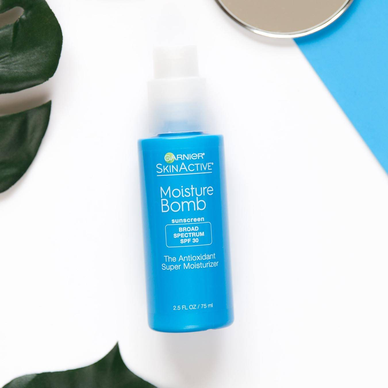 Garnier SkinActive Moisture Bomb Sunscreen Broad Spectrum SPF 30 The Antioxidant Super Moisturizer on a white background next to palm fronds and a mirror partially sitting on a blue piece of paper.