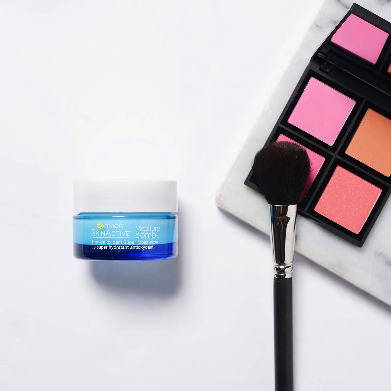 Garnier SkinActive Moisture Bomb The Super Antioxidant Super Moisturizer on a white background next to a palette of pink and orange blushes on a marble slab with a makeup brush.