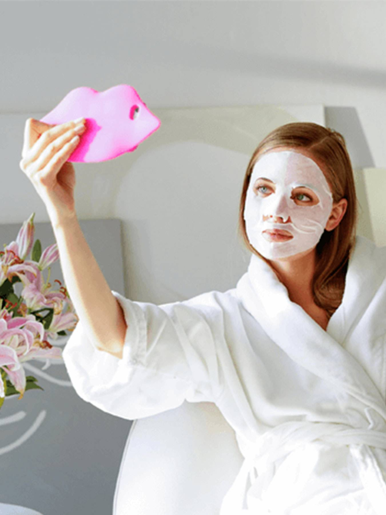 A woman wearing a white bathrobe and The Super Hydrating Sheet Mask - Anti-Fatigue sitting on a white chair holding up a pink lip-shaped mirror in a white and gray room with pink and white flowers on a reflective table.