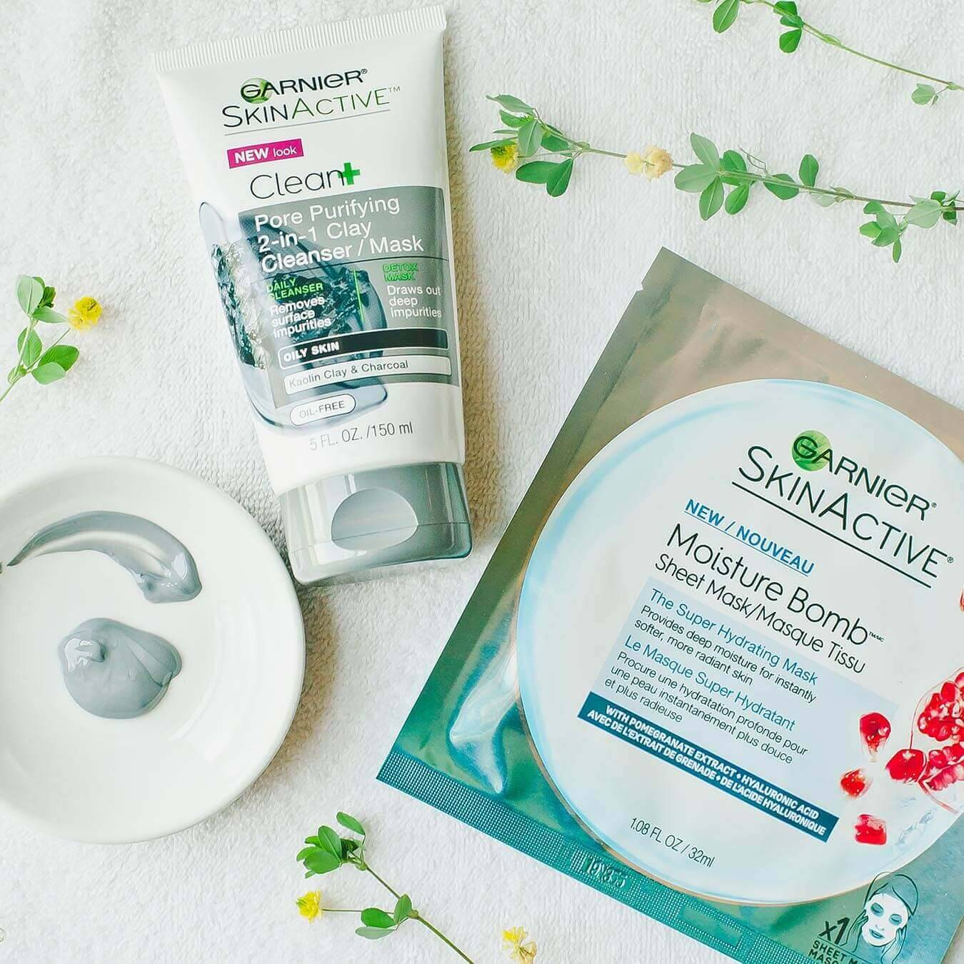 Garnier SkinActive Moisture Bomb Sheet Mask with Pomegranate Extract next to SkinActive Clean+ Pore Purifying 2-in-1 Clay Cleanser/Mask and a white dish with some cleanser/mask squeezed from the tube and smeared in an arc on a white towel strewn with yellow wildflowers.