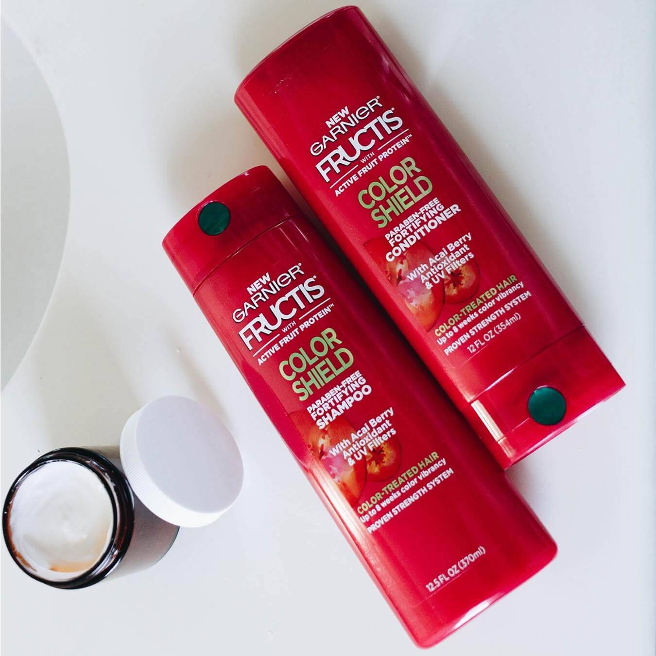 Garnier Fructis Color Shield Fortifying Shampoo and Fructis Color Shield Fortifying Conditioner on a white table next to an open facial cream container.