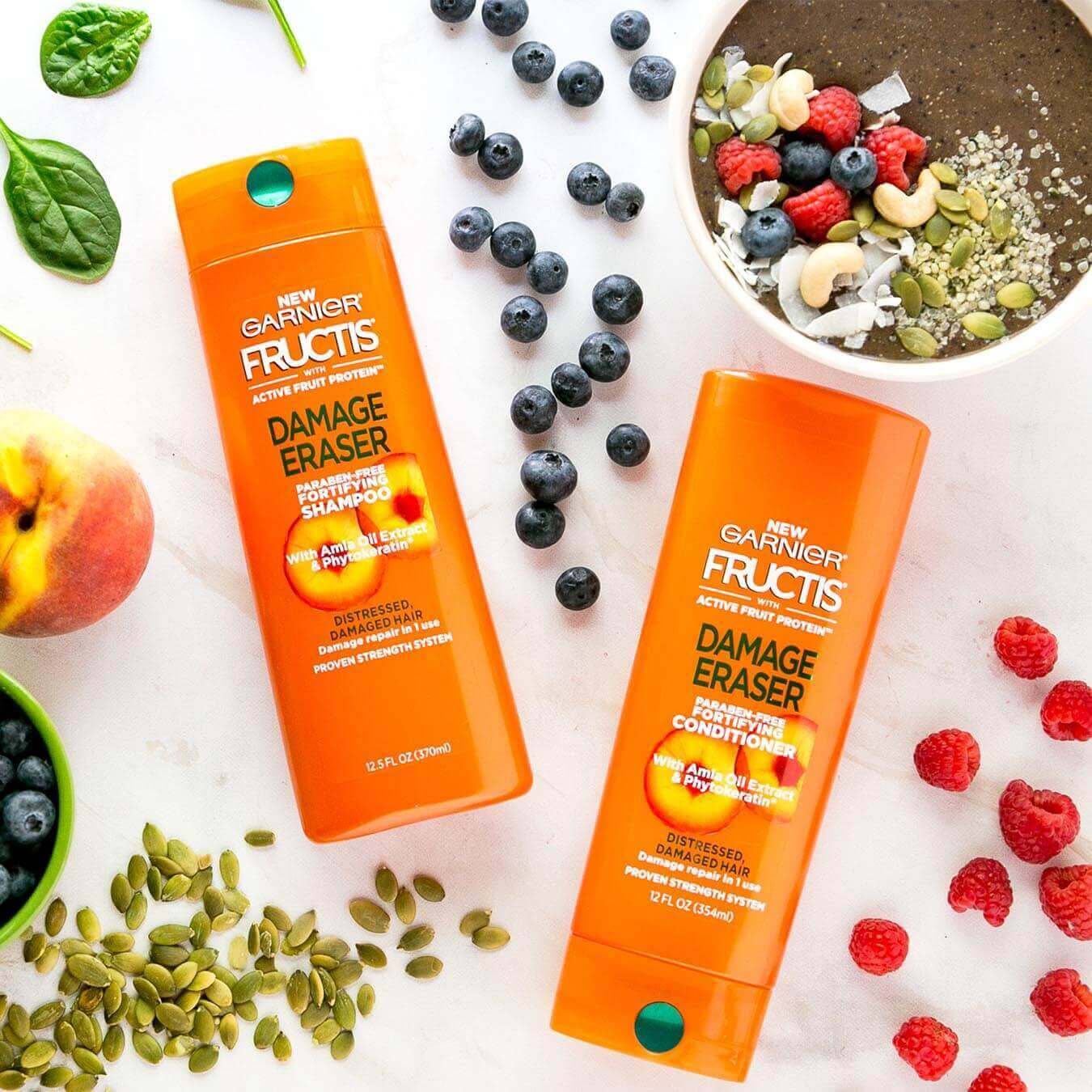 Garnier Fructis Damage Eraser Shampoo and Damage Eraser Conditioner on white marble next to raspberries, blueberries, basil leaves, pumpkin seeds, and soil with various toppings.