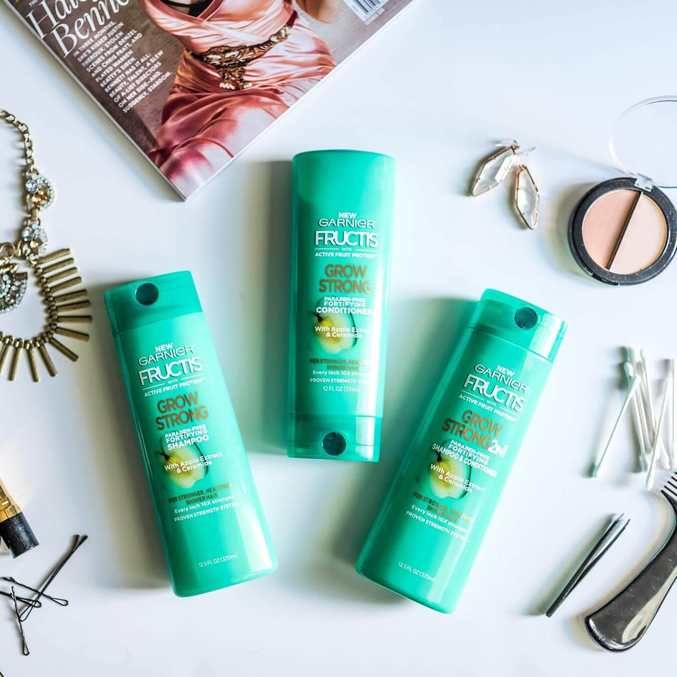 Garnier Fructis Grow Strong Shampoo, Fructis Grow Strong Conditioner, and Fructis Grow Strong 2-in-1 on a blueish-white background next to gold earrings and necklace, bobby pins, tweezers, q-tips, a comb, and two shades of blush.