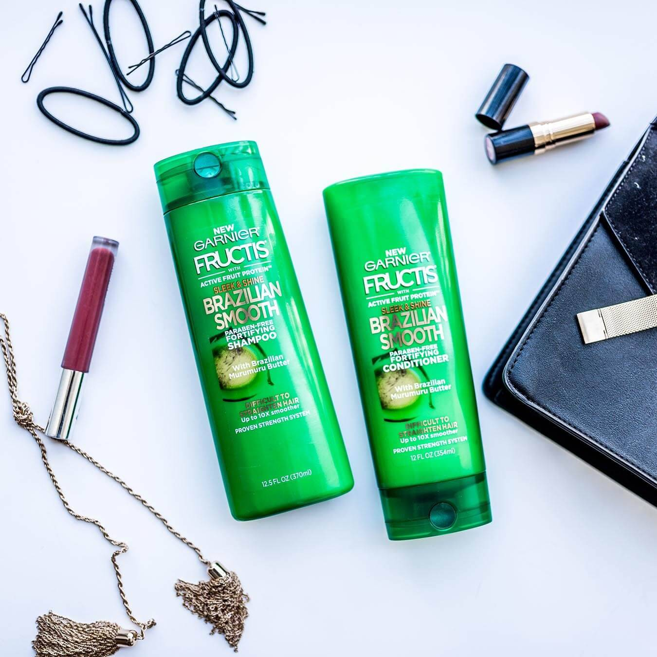 Garnier Fructis Brazilian Smooth Shampoo and Brazilian Smooth Conditioner on a blue background next to a leather purse, an open red lipstick, lip gloss, a knotted metal gold tassel, and several bobby pins and hair ties.