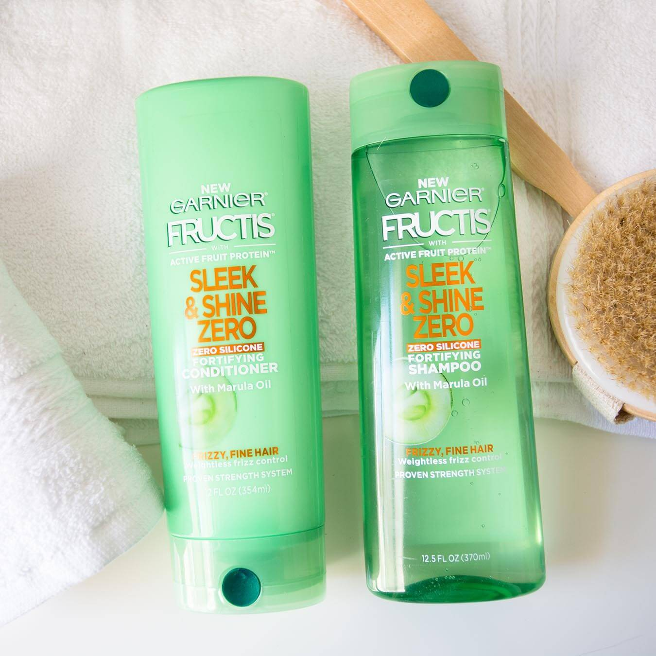 Garnier Fructis Sleek & Shine Zero Shampoo and Fructis Sleek & Shine Zero Conditioner on a white bath towel on a white background next to a white hand towel and a wooden bath scrub brush.