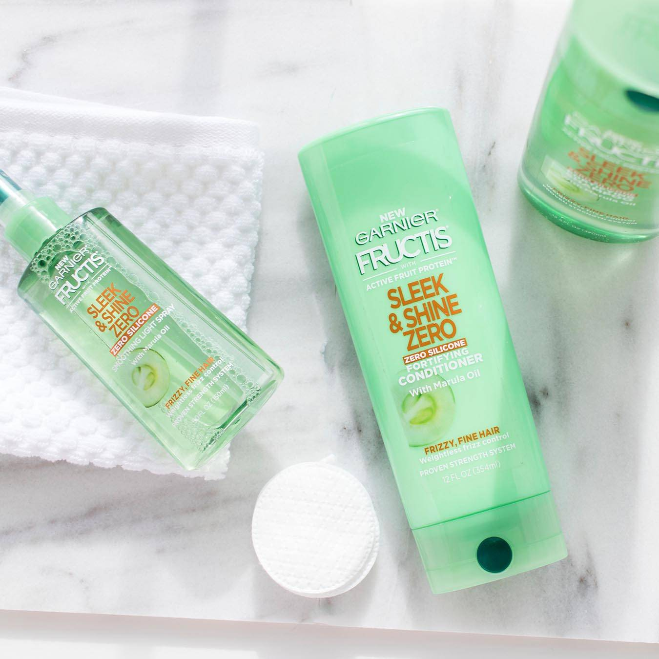 Garnier Fructis Sleek & Shine Zero Shampoo and Fructis Sleek & Shine Zero Conditioner on white marble and Fructis Sleek & Shine Smoothing Light Spray on a white wash cloth next to makeup removal pads.
