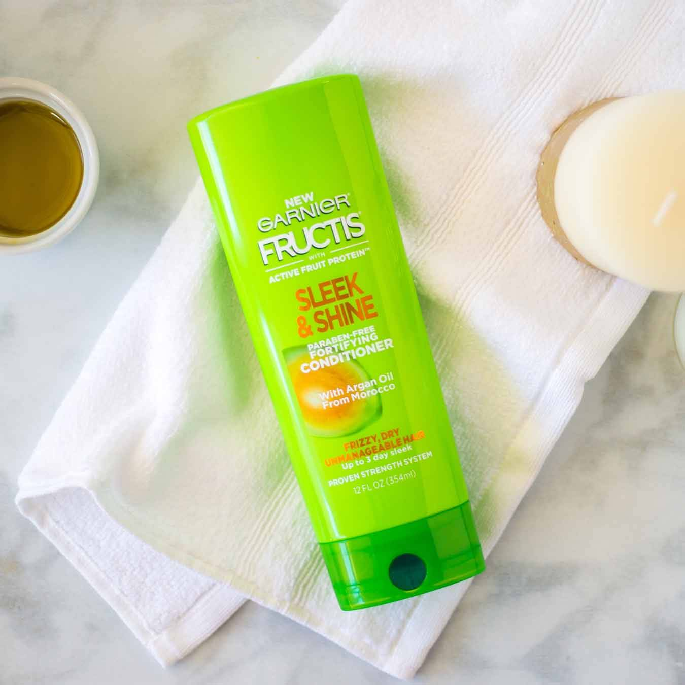 Garnier Fructis Sleek & Shine Conditioner on a white hand towel on white marble next to an unlit white candle and a ramekin of oil.