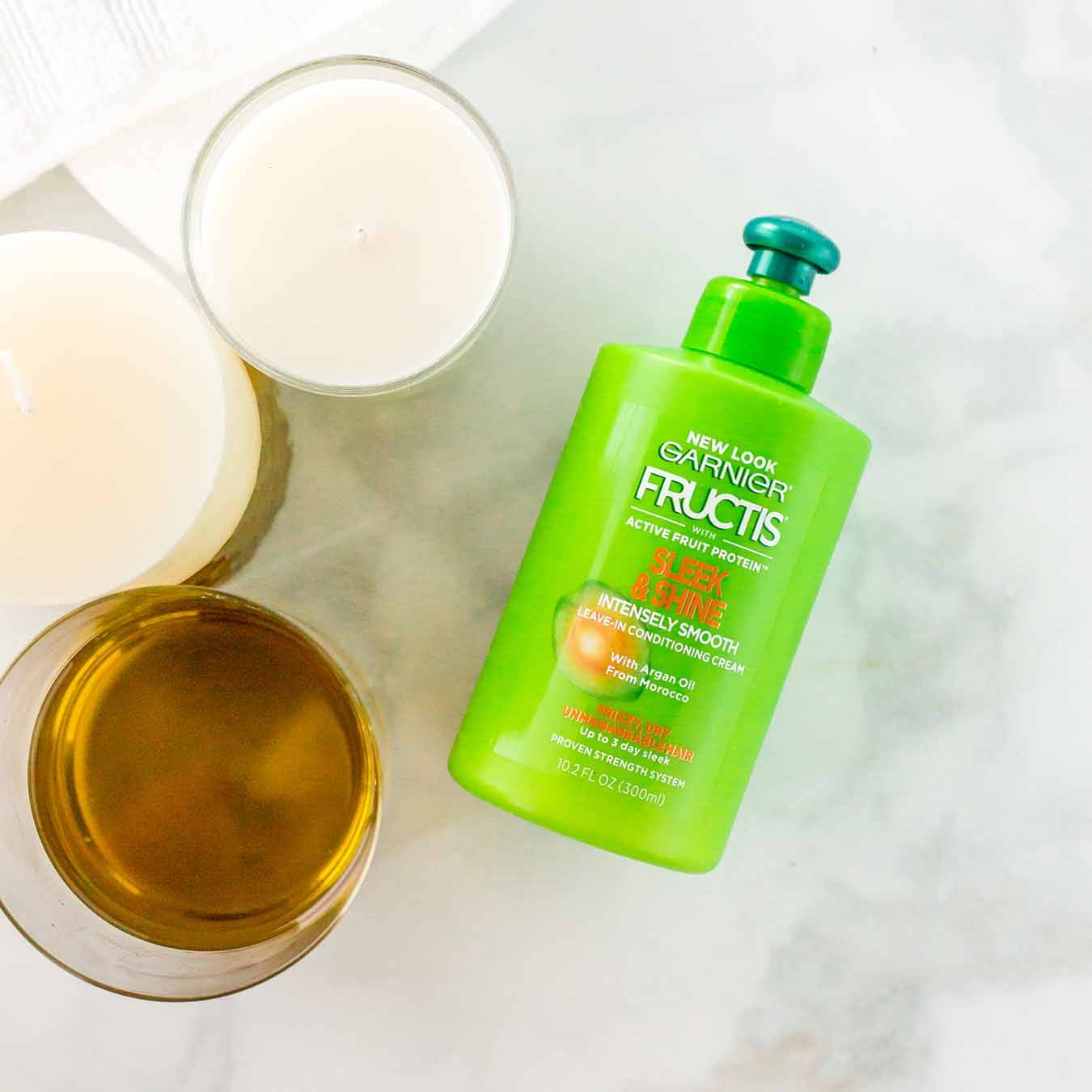 Garnier Fructis Sleek & Shine Leave-In Conditioner on white marble next to a white hand towel, white candles, and a glass of oil.