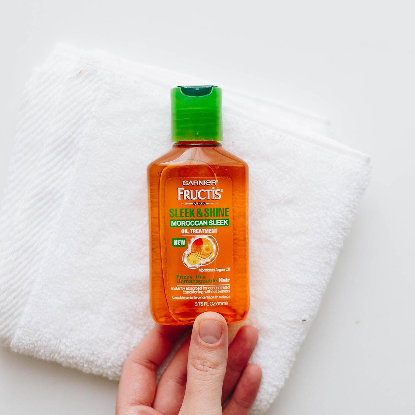 Garnier Fructis Sleek & Shine Moroccan Sleek Oil Treatment being held above a folded white hand towel on a white background.