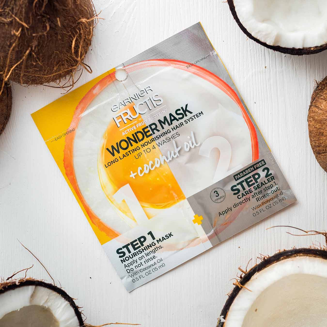 Garnier Fructis Wonder Mask with Coconut Oil on white-painted wood and halved coconuts.
