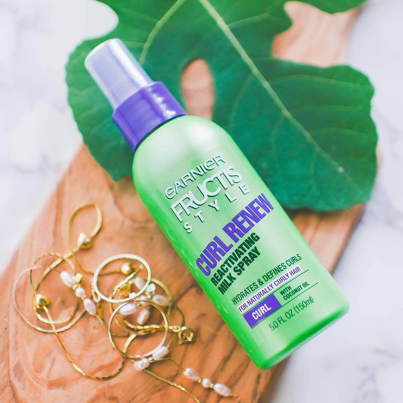 Garnier Fructis Style Curl Renew Reactiving Milk Spray on a wooden oar next to a large sassafras leaf and gold jewelry.
