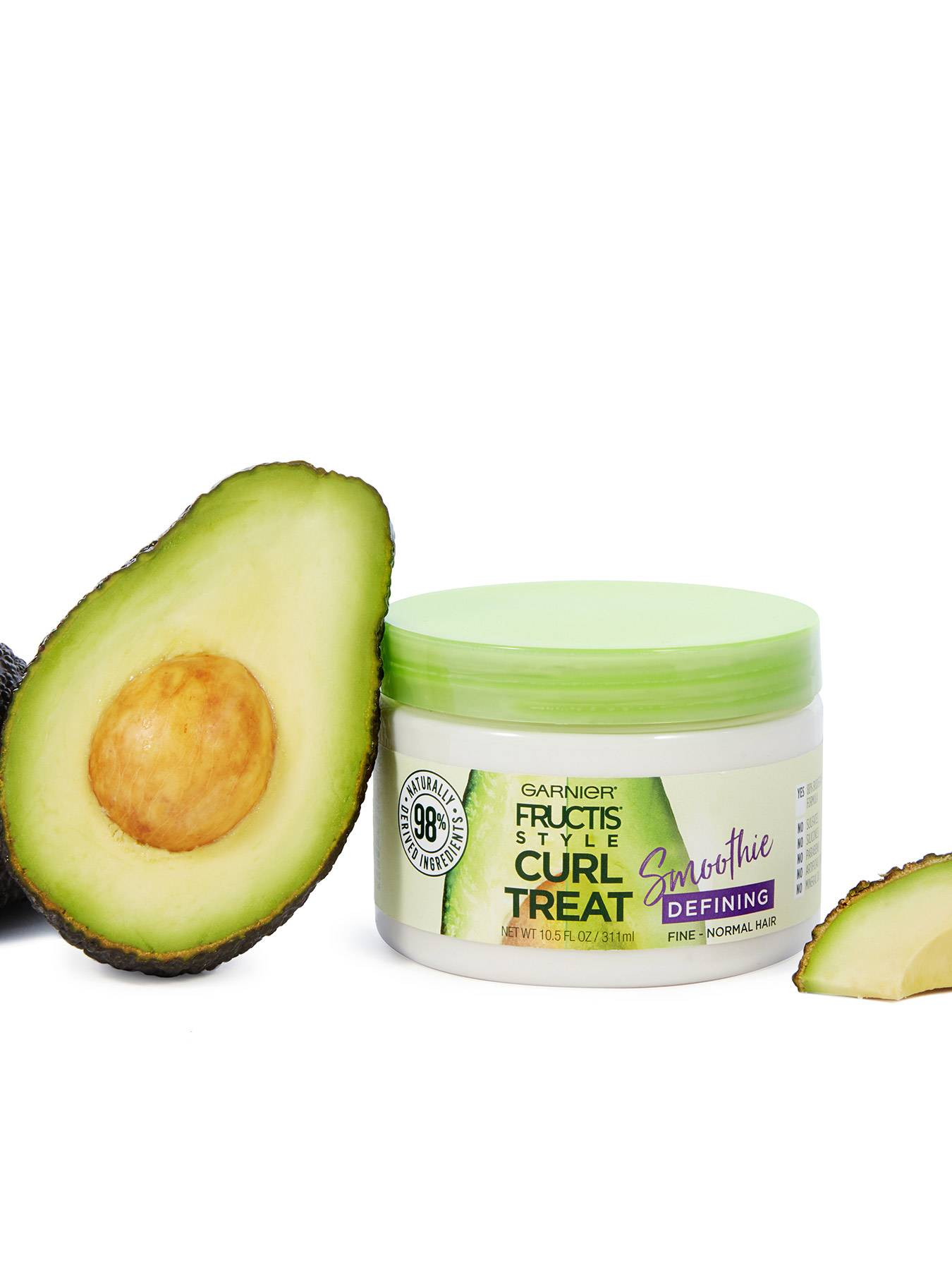 Curl Treat Smoothie Defining Leave-in Styler for Soft Curls next to avocado halves.