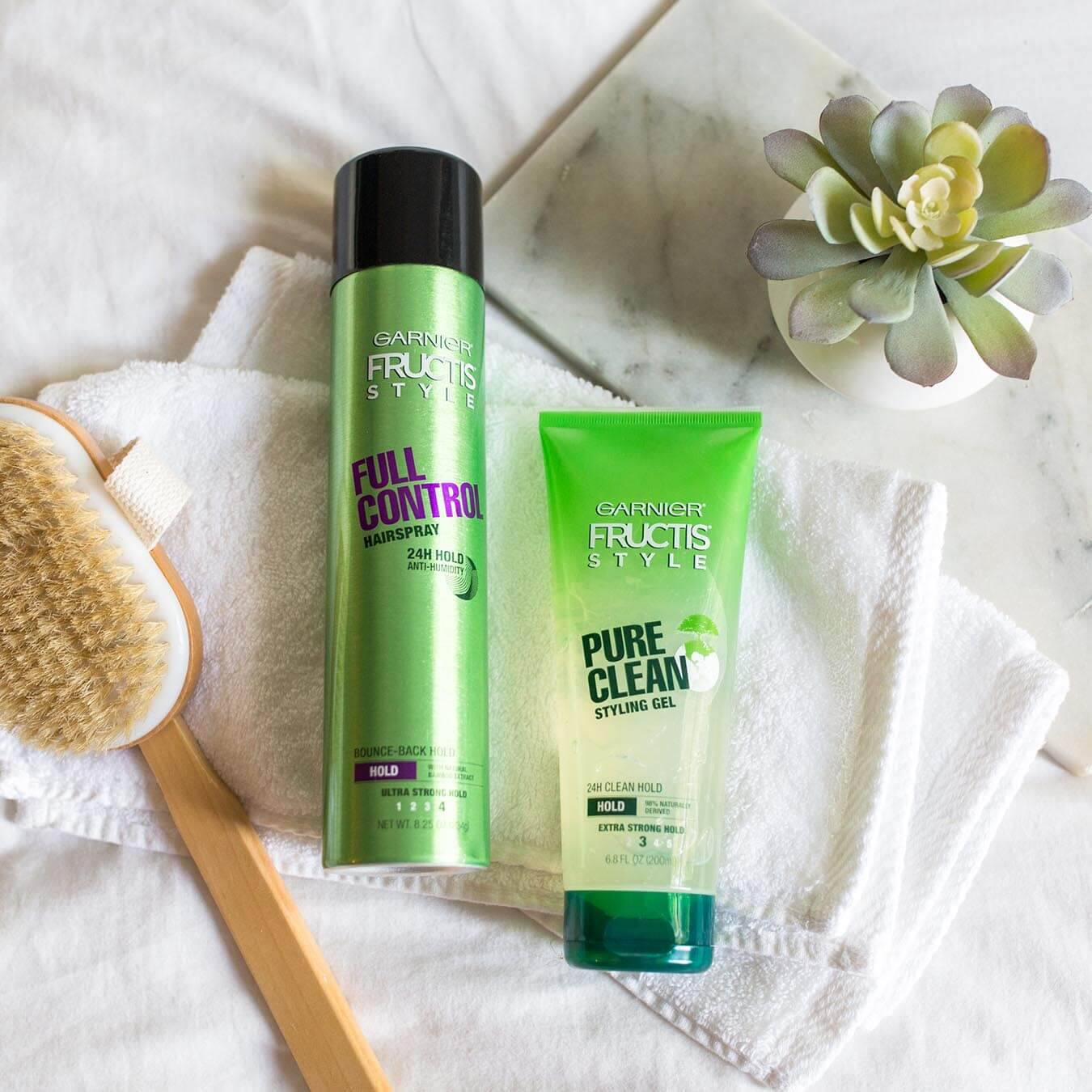 Garnier Fructis Style Full Control Hairspray and Fructis Style Pure Clean Styling Gel on two white wash cloths next to a wooden long-handled scrub brush and a potted succulent.