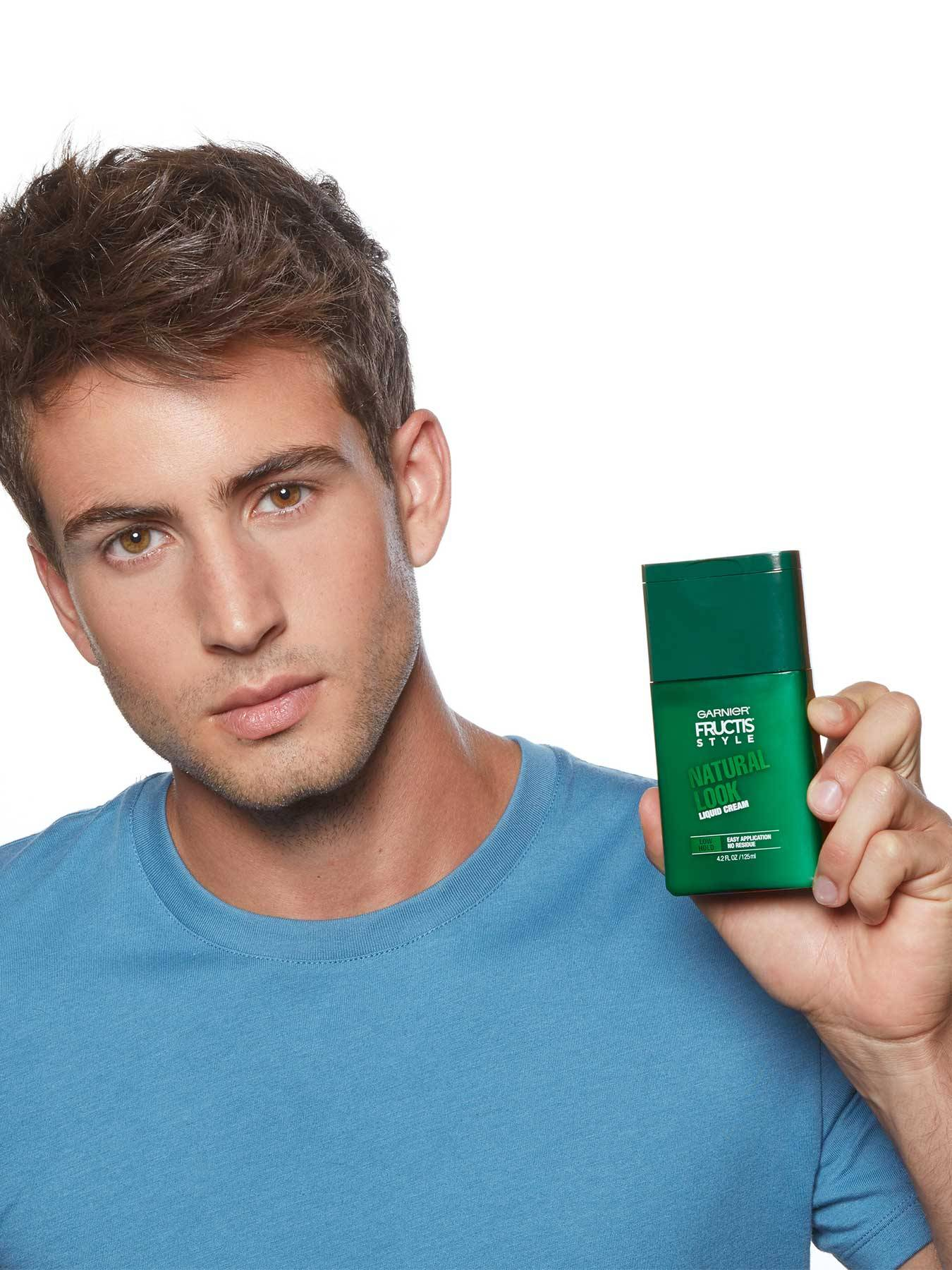 Model holding Natural Look Liquid Hair Cream for Men, No Drying Alcohol.