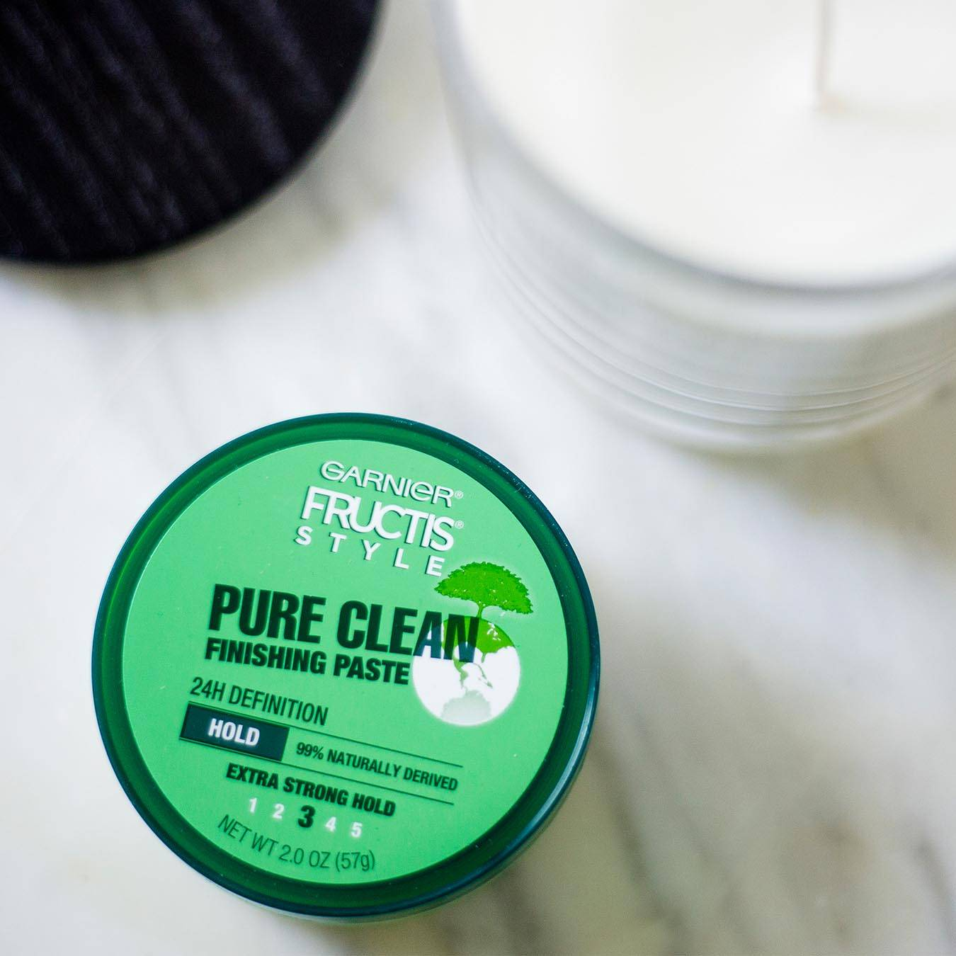 Garnier Fructis Style Pure Clean Finishing Paste on white marble next to a white candle and black lid.