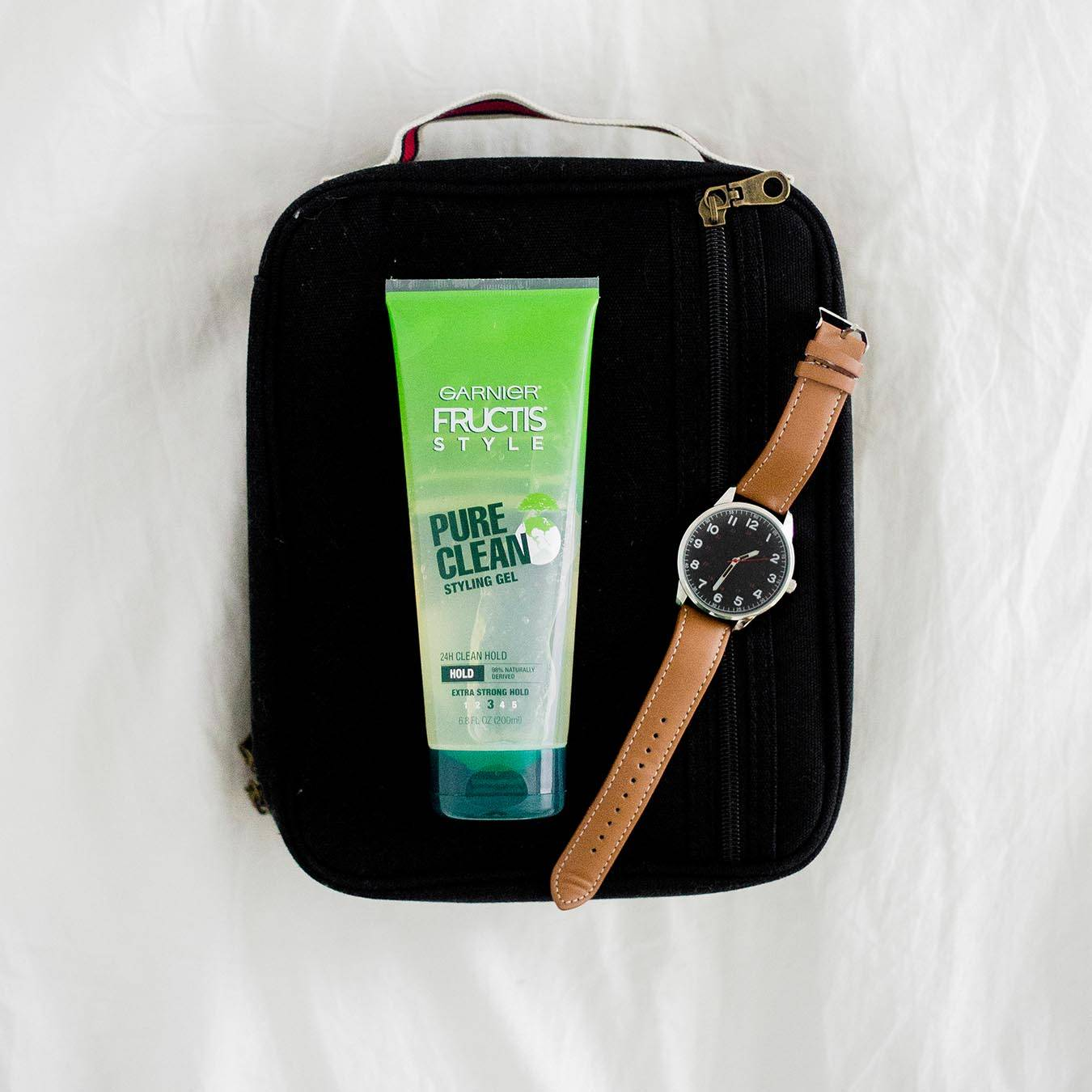 Garnier Fructis Style Pure Clean Styling Gel next to a watch with a black face and brown band on a black travel bag on white cloth.