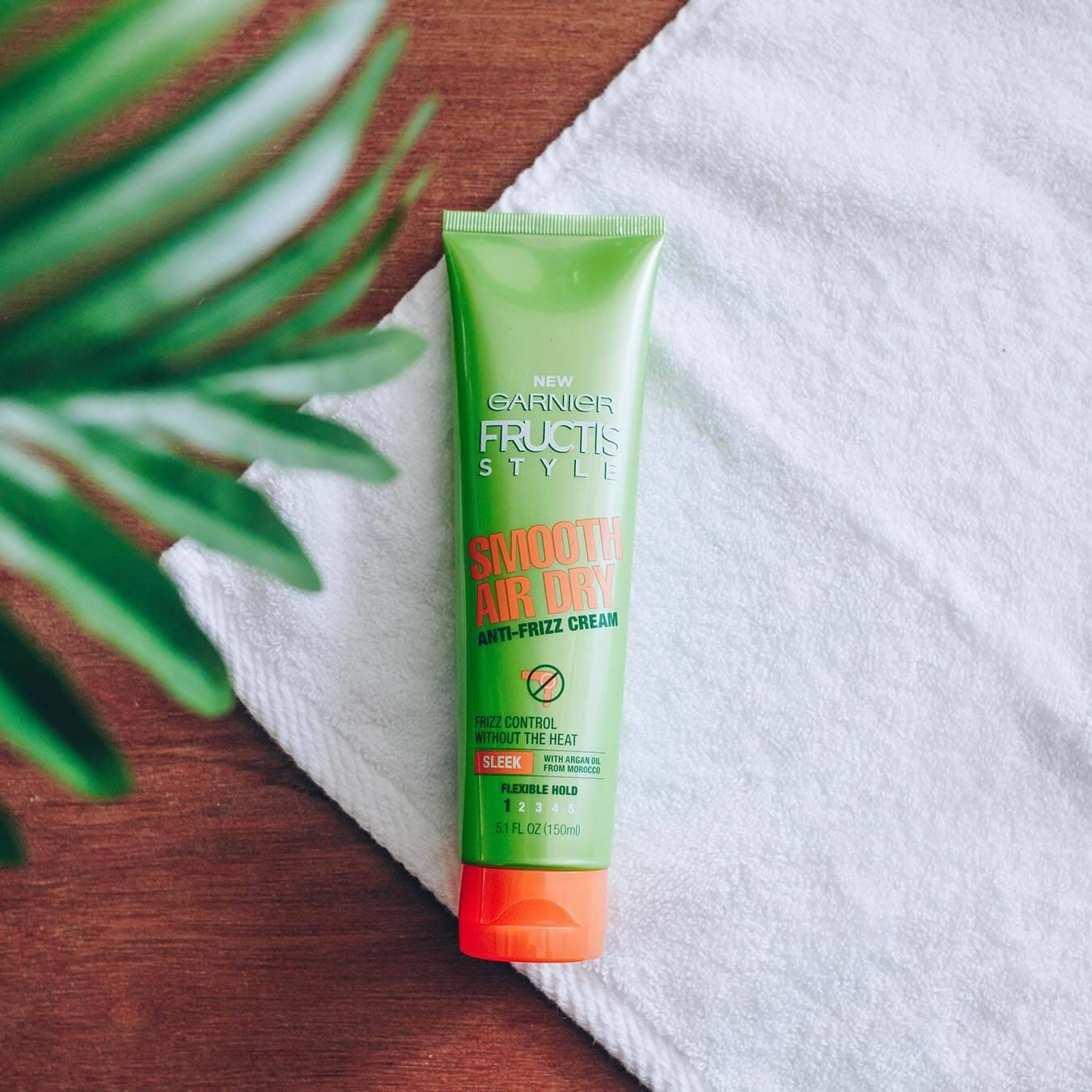 Garnier Fructis Style Smooth Air Dry Anti-Frizz Cream on a white hand towel on wood with a branch of leaves in the foreground.