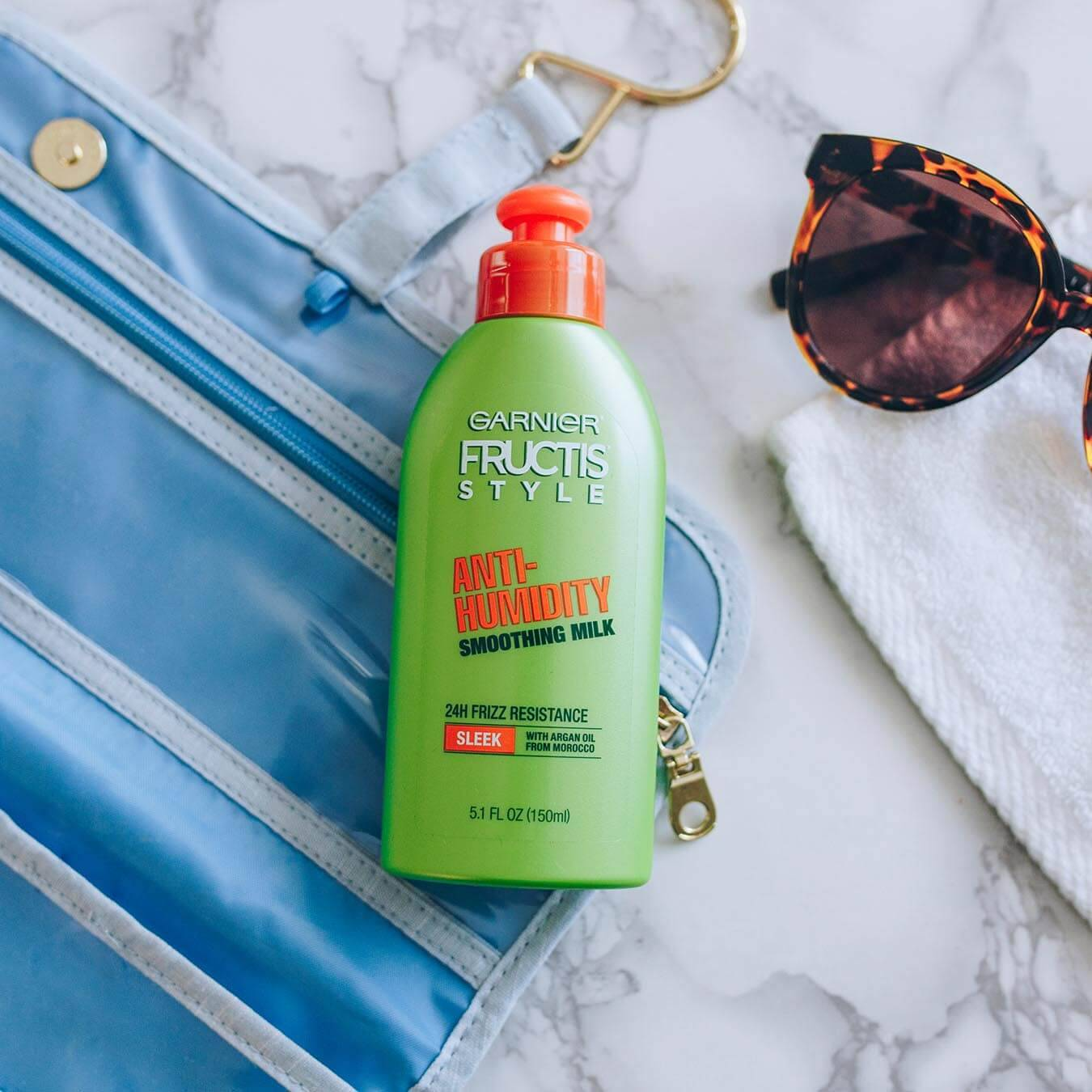 Garnier Fructis Style Anti-Humidity Smoothing Milk on a blue fold-out travel kit on white marble next to leopard-print sunglasses on a white wash cloth.