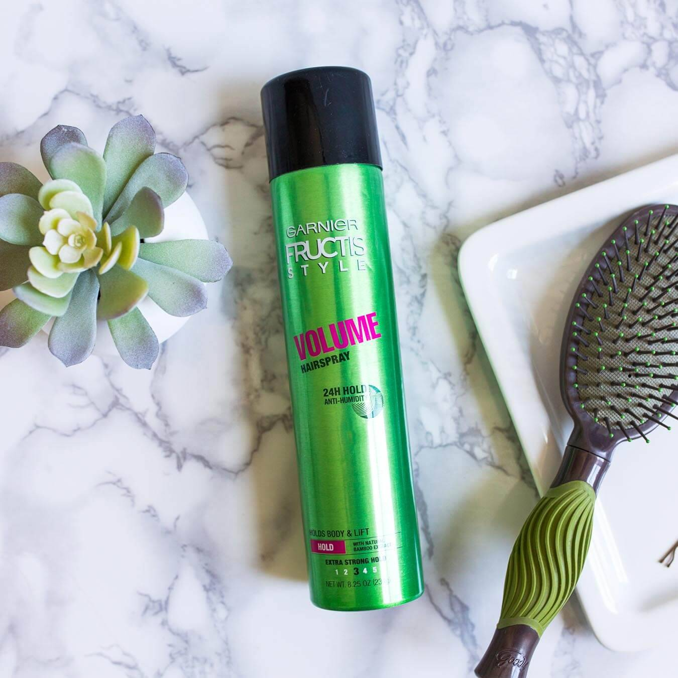 Garnier Fructis Style Volume Hairspray on white marble next to a potted succulent and a white tray holding a bobby pin and a green and brown brush.