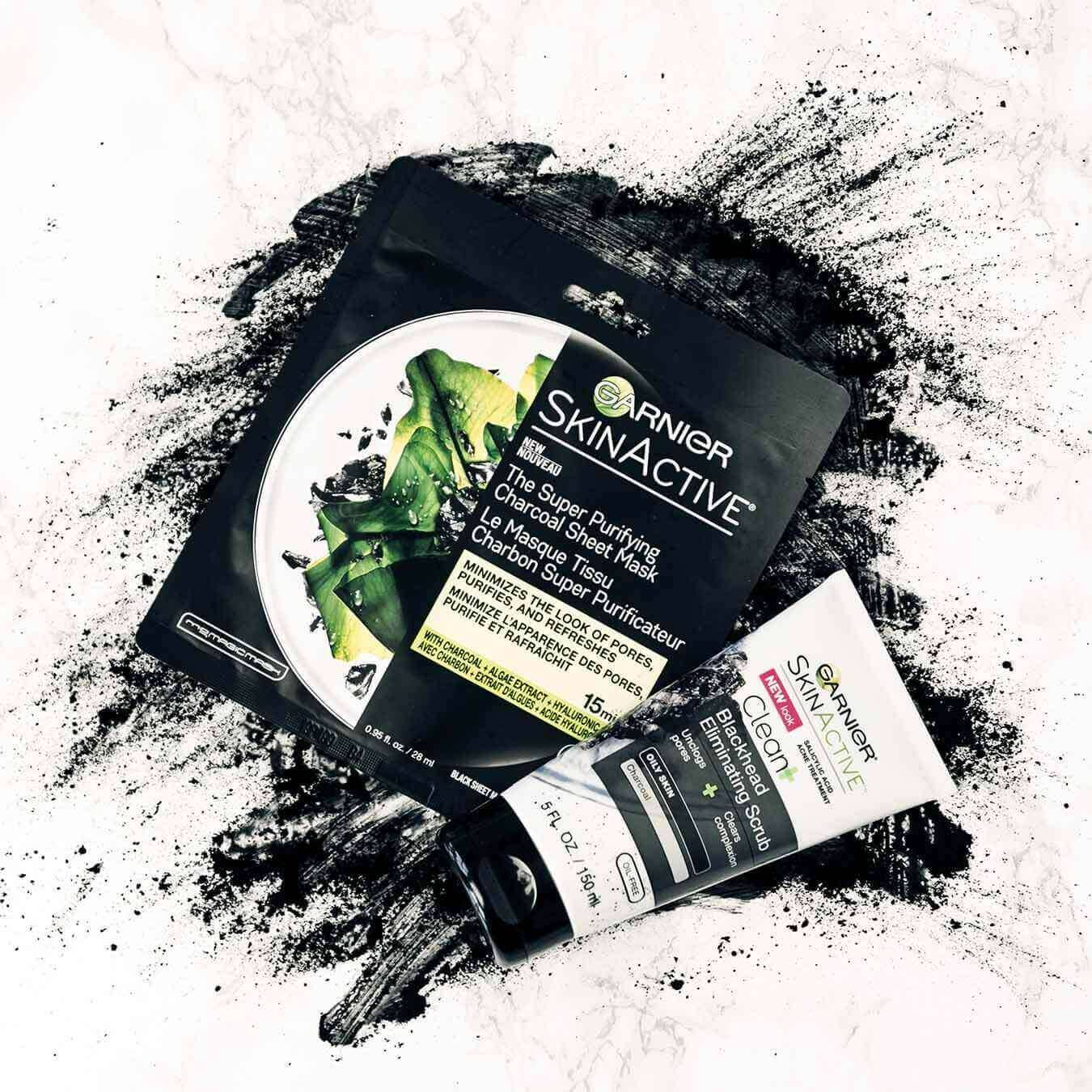 Garnier SkinActive Super Purifying Charcoal Sheet Mask and SkinActive Clean+ Blackhead Eliminating Scrub on an explosion of charcoal powder on pinkish white marble.