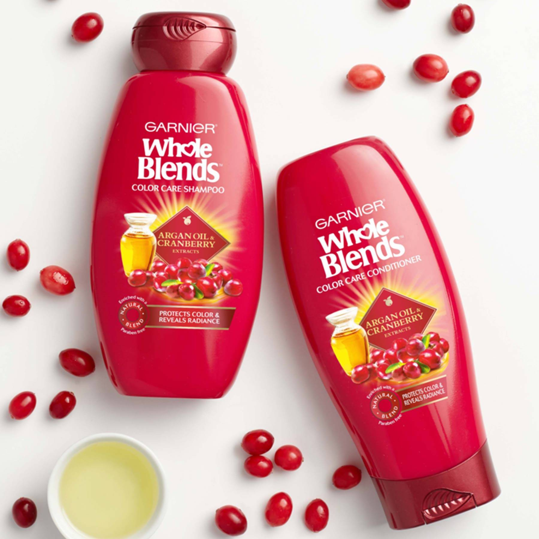 Whole Blends Color Care Shampoo with Argan Oil and Cranberry and Color Care Conditioner with Argan Oil and Cranberry on a white background strewn with whole cranberries and a ramekin of oil.